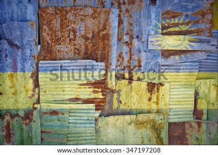 An abstract background image of the flag of Rwanda painted on to rusty corrugated iron sheets overlapping to form a wall or fence. - stock photo