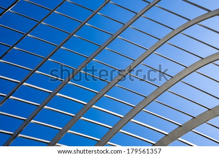 An abstract background texture of a lattice structure highlighted against a deep blue sky.