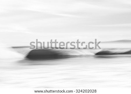 An abstract, black and white seascape featuring crashing ocean waves.  Image made with panning motion and a long exposure for a soft, blurred effect. - stock photo