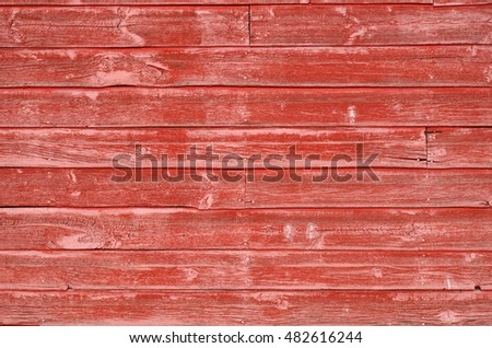 An abstract image of fading red paint on an old wooden building exterior.