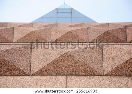 An abstract image of tan colored bricks and a glass pyramid.