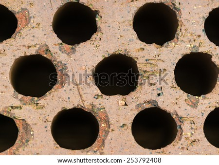 An abstract macro shot of the holes in top of a brick. - stock photo