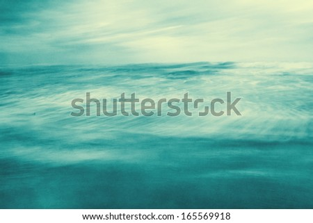 An abstract ocean seascape with blurred motion and a long exposure.  Image displays a retro, vintage look with cross-processed colors and a pleasing paper grain and texture.