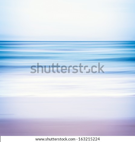 An abstract ocean seascape with blurred panning motion.  Image displays a blue and purple split-toned color scheme. - stock photo