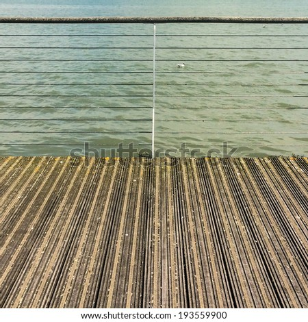An abstract shot of a boardwalk leading to a fence with the sea beyond.