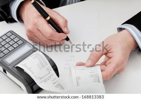 An accountant going through company's finances summing up the expenses