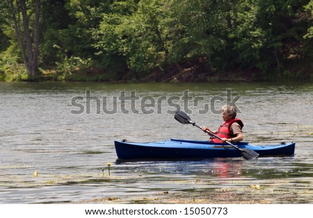 An active female senior citizen paddling around in a kayak.