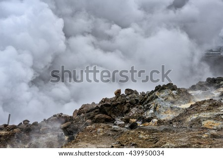 An active hot spring geyser in Iceland spews hot steam and sulphur continuously from the earth's core against a rocky volcanic landscape - stock photo