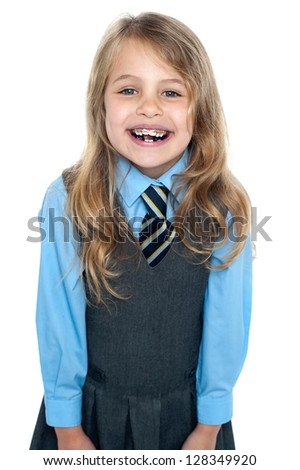 An active kid with a bright smile in school uniform expressing her happiness. - stock photo