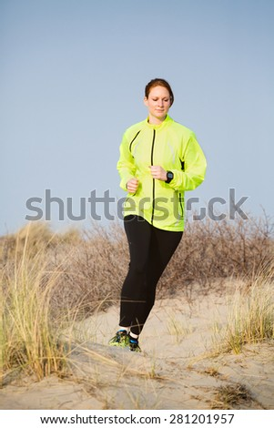 An active young Caucasian woman runs cross country over a beach with dunes and grass.
