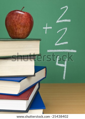 An addition on the chalkboard with an apple on top of a pile of books. - stock photo