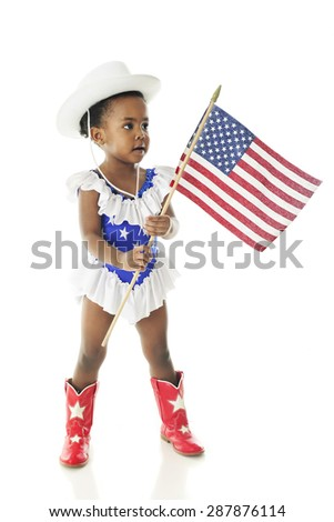 An adorable African American two year old prepared to march in a parade in her western majorette outfit of star-studded red, white and blue and carrying an American flag.  On a white background. - stock photo