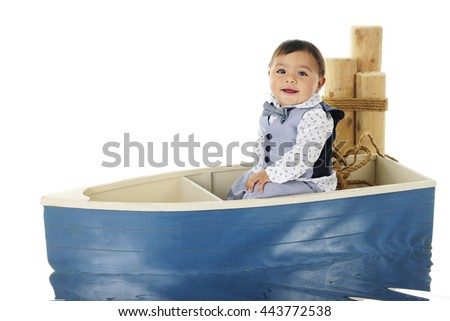 An adorable baby boy happily sitting in a small row boat next to mooring posts.  On a white background. - stock photo