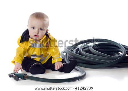 An adorable baby boy in a fireman's suit, reaching for a hose.  Isolated on white. - stock photo