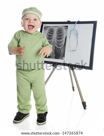 An adorable baby boy in green scrubs laughing as he stands before an easel displaying a human chest x-ray and stethoscope.  On a white background. - stock photo