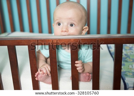 An Adorable baby boy in his crib  - stock photo