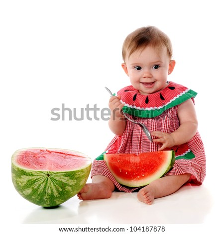 An adorable baby girl happily eating a watermelon in a watermelon sundress.  On a white background. - stock photo