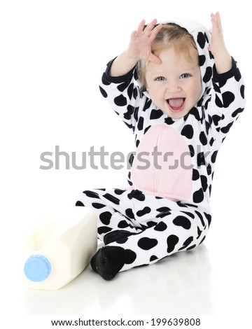 An adorable baby girl laughing excitedly in her holstein cow costume. She sits by a half gallon of milk. On a white background.