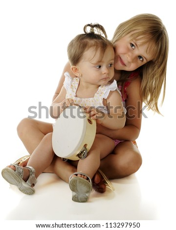 An adorable baby girl looking back at her sister who's happily holding her on her lap.  On a white background.