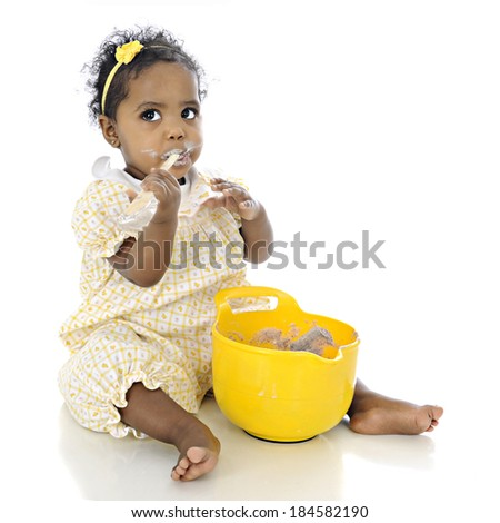 An adorable baby girl looking up questioningly while eating pudding from a mixing bowl before her.  On a white background. - stock photo