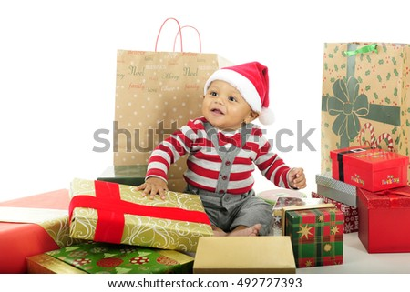 An adorable baby happily sitting in his Santa hat and surrounded by wrapped gifts.  On a white background.