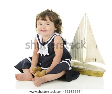 An adorable baby sailor girl happily sitting with her toy sailboat behind her.  On a white background. - stock photo
