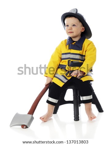 "An adorable barefoot 2-year-old ""fireman"" sitting on a stool with his hatchet in hand.  On a white background."