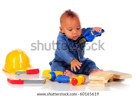 An adorable biracial baby in workman overalls eagerly playing with plastic tools.  isolated on white.