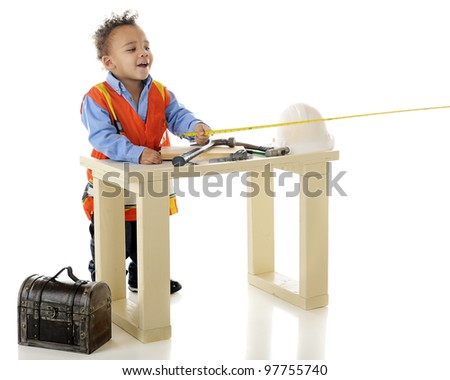 "An adorable biracial preschooler measuring while playing ""construction worker"" at his tool bench.  On a white background. - stock photo"