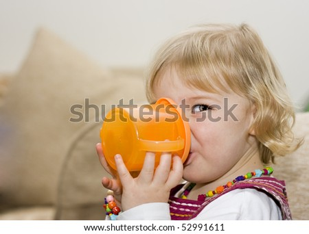 An adorable cute little girl drinking from a training cup
