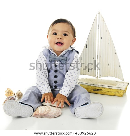 An adorable, dressed up baby boy delighted with his sea shells.  A toy sailboat is nearby.  On a white background.