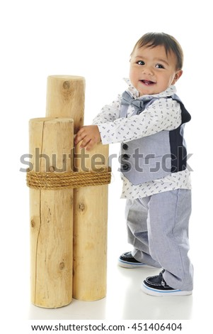 An adorable, dressed up baby boy holding on 3 mooring posts as he steadies himself for standing.  On a white background. - stock photo