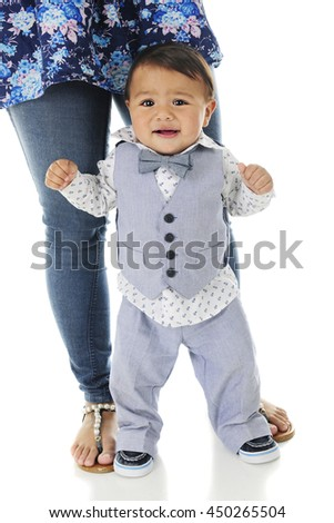 An adorable, dressed-up baby boy looking mighty worried as he stands without hanging on.  His mother's legs and feet are securely behind him giving him some support.  On a white background. - stock photo