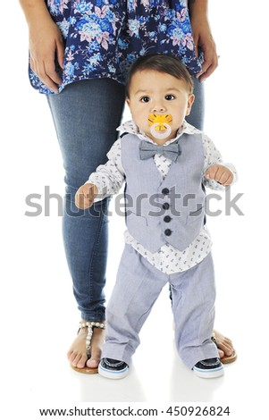 An adorable, dressed up baby boy, standing nervously against his mother's legs -- ready to walk, but feeling insecure.  On a white background. - stock photo