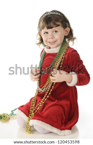An adorable, dressed up preschooler happily waring multiple strands of shiny Christmas beads.  On a white background.