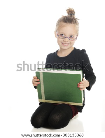 An adorable elementary girl looking studiously at the viewer over her glasses.   He holds a giant textbook on her lap.  On a white background.