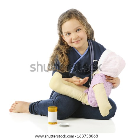 "An adorable elementary""nurse"" in scrubs preparing to give her doll some pills.  On a white background. - stock photo"