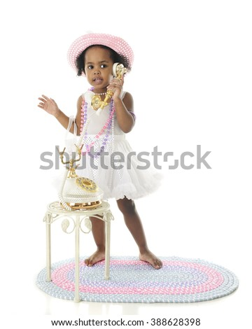 An adorable girlie girl standing in her petticoat, pearls and hat while talking on a fancy French phone.  On a white background. - stock photo