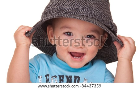 An adorable Hispanic baby is holding a hat.  Image is isolated on white with reflection.