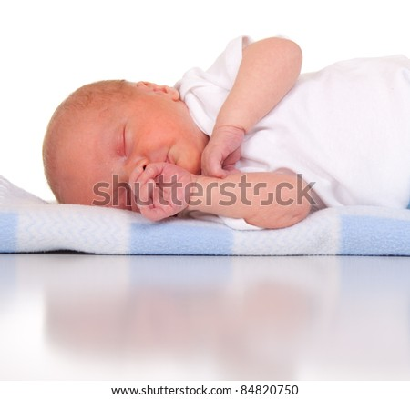 An adorable image of a two week old baby boy.  Image is isolated on white with reflection. - stock photo