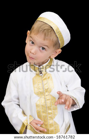 An adorable little boy dressed in Arabian thobe, isolated on black. - stock photo