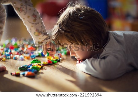 An adorable little boy playing with tiny toys lying on the floor - stock photo
