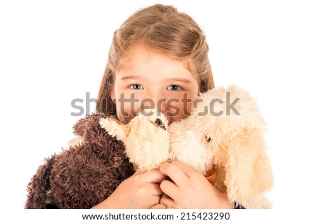 An adorable little girl holding three plush toys close to her face. Isolated on white.