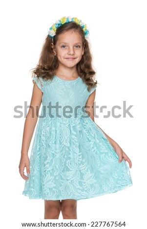 An adorable little girl in a blue dress is standing on the white background - stock photo