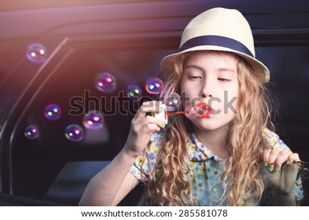 An adorable little girl in a hat lets soap bubbles in car - stock photo
