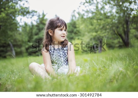 An adorable little girl in the forest meadow