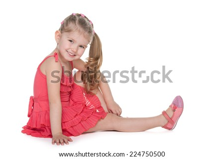 An adorable little girl is sitting on the floor on the white background - stock photo