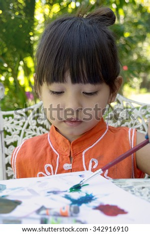 An adorable little girl with Chinese outfit style painting her art work  - stock photo