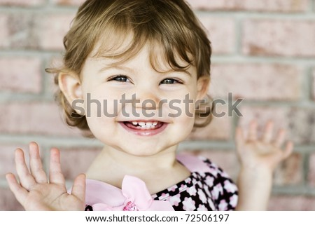 An adorable little girl with very expressive happy face, selective focus on face with blurred background