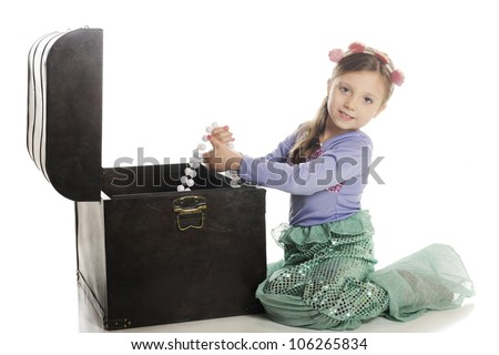 An adorable little mermaid pulling strands of large pearls from an old treasure chest.  On a white background. - stock photo